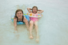 Girls in ocean. Two girls  with their tubes around them while laying in the ocean Royalty Free Stock Images
