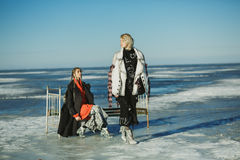 Girls in old clothes with a bed on the frozen sea Royalty Free Stock Photo