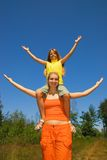 The girls with open arms. The girls with wide open arms, clear blue sky behind them Royalty Free Stock Photo