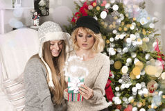 Girls open Christmas presents near Christmas tree Stock Photos