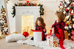 Girls opening Christmas presents. Two adorable girls in checkered dresses sitting near Christmas tree and opening their presents Royalty Free Stock Images