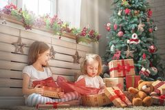 Girls opening gifts. Merry Christmas and Happy Holidays! Cheerful cute childrens girls opening gifts. Kids wearing pajamas having fun near tree in the morning Royalty Free Stock Photography