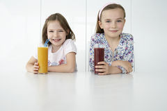 Girls With Orange And Chocolate Drinks At Table Stock Images