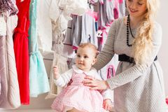 Girls out shopping for clothes. Cute beautiful little girl with her mother buying dress in shop Stock Photo