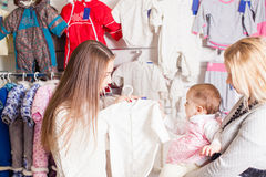Girls out shopping for clothes. Cute beautiful little girl with her mother buying dress in shop Stock Image
