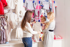 Girls out shopping for clothes. Cute beautiful little girl with her mother buying dress in shop Stock Photos