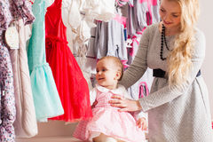 Girls out shopping for clothes. Cute beautiful little girl with her mother buying dress in shop Royalty Free Stock Photo