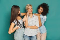 Girls overhearing her friend mobile phone talk. At home. Young women having fun, making group conversation, copy space Royalty Free Stock Image