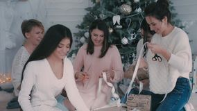Girls pack Christmas gifts near a Christmas tree stock footage