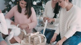 Girls pack Christmas gifts near a Christmas tree stock video