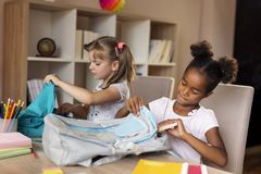 Girls packing school bags stock photography