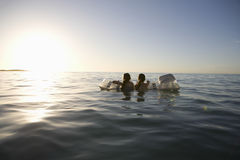 Girls Paddling Out To Sea On Air Mattress Royalty Free Stock Photo