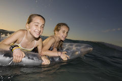 Girls Paddling Out To Sea On Air Mattress Royalty Free Stock Images