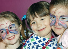 Girls with painted faces. Three young girls with face paint at a party stock photo