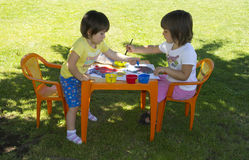 Girls painting. With colors and brushes in the garden Royalty Free Stock Photography