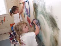 Girls painting wall Stock Image