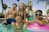 Girls With Parents And Grandmother In Swimming Pool. Portrait of smiling two girls with parents and grandmother in the swimming pool Stock Image