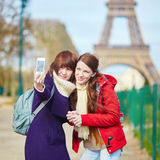 Girls in Paris doing selfie near the Eiffel tower Royalty Free Stock Photos