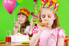 Girls party horns. Girls in birthday crowns playing with party horns Stock Photo
