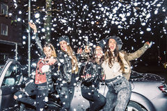 Girls partying. Pretty crazy girls dancing, throwing confetti and drinking wine - Young women partying outdoors before to go in a club royalty free stock photography