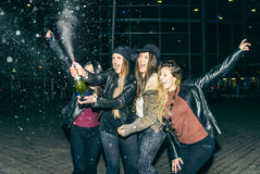 Girls partying and uncorking champagne bottle. Four pretty girl celebrating something outdoors - Women opening and sprinkling a white wine bottle - Group of Royalty Free Stock Photography