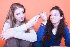 Girls passing a cell phone Stock Photography