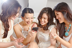 Girls paying with cell phone Stock Images