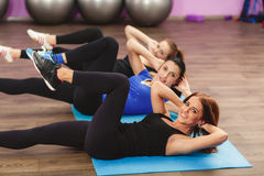 Girls perform exercises for abdominal muscles. Royalty Free Stock Photography