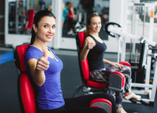 Girls perform leg exercises on the simulator. Two happy women in a fitness center holding their thumbs up royalty free stock photography