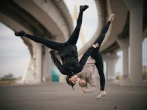Girls perform splits in the air while jumping on the urban background of the bridge royalty free stock photography