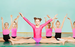 Girls performing splits during gymnastics class. Portrait of preteen girls in sportswear performing side splits during gymnastics class, sitting against blanked Stock Image