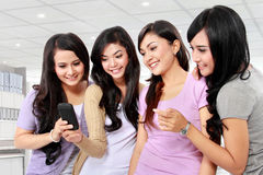 Girls with phone. Group of girls looking at phone together Stock Images