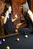 Girls on phone in poolroom  Royalty Free Stock Images