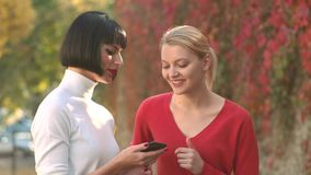 Girls with phone. Two girls using smart phone. Business outdoor. Young bloggers, blog concept. Outdoor portrait of girls stock video