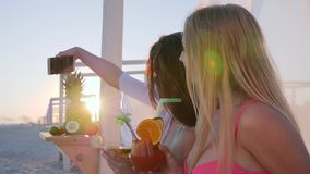 Girls photographed on mobile phone Holiday pictures, Selfphoto, exotic fruits on beach, stock video footage