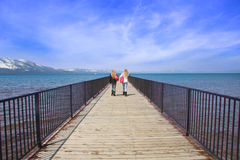 Girls on Pier. Two teen girls walking toward a view on a pier over  Lake Tahoe Royalty Free Stock Images