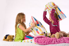 The girls pillow fight. Two young children enjoying their colorful bed stock image