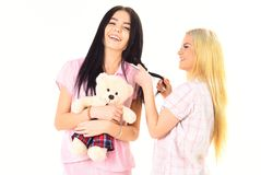 Girls in pink pajamas, isolated white background. Ladies on smiling faces with plush toy bear look cute. Girlish leisure. Concept. Sisters, best friends in royalty free stock image