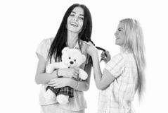 Girls in pink pajamas, isolated white background. Ladies on smiling faces with plush toy bear look cute. Girlish leisure. Concept. Sisters, best friends in stock photos