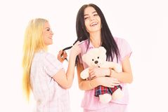 Girls in pink pajamas, isolated white background. Ladies on smiling faces with plush toy bear look cute. Girlish leisure. Concept. Sisters, best friends in royalty free stock photography