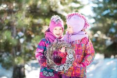 Girls in pink suits hold a Christmas wreath in winter. Children`s winter holidays. Girls in pink ski suits hold a Christmas wreath in winter. Children`s winter stock images