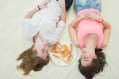 Girls with pizza. Happy overeat girls lying with pizza pieces Royalty Free Stock Photo