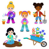 Girls planting flowers and working in the garden. Royalty Free Stock Photo