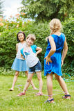 Girls play chinese jump rope in garden Stock Image