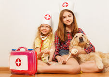 Girls play cute doctors bandaging their pet dog Stock Photo