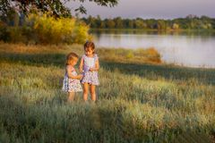 Girls play the field, the general plan. Girls play the field at a pond at sunset Stock Images