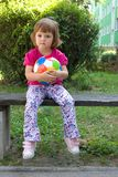 Girls play football. Little, cute girl with colorful football outdoors Royalty Free Stock Photo