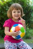 Girls play football. Little, cute girl with colorful football outdoors Stock Photos