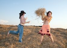 Girls play with hay. Country girls play with hay  against sky Stock Photos
