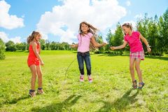 Girls play jumping over the rope. Three girls jumping over the rope in the park, having fun in active games outside Royalty Free Stock Images